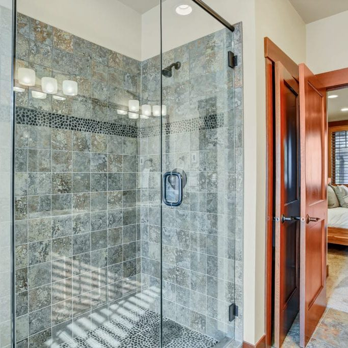 Master bathroom with glass walk in shower and gray tile surround . Northwest, USA
